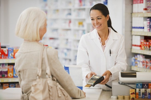 A smiling female pharmacist across the counter from female customer in drugstore