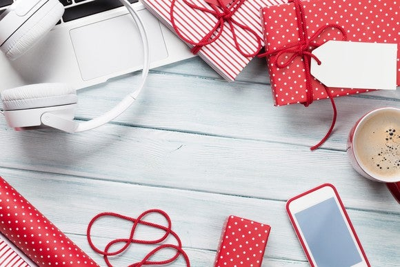 Wrapped presents, a laptop, a set of headphones, a smartphone, and a cup of coffee sitting on a table