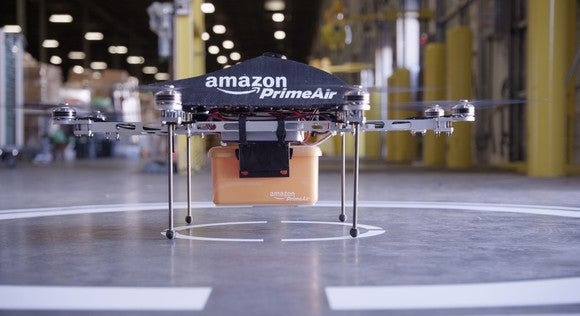 "A package-delivery drone marked ""Amazon PrimeAir"", on a landing pad."