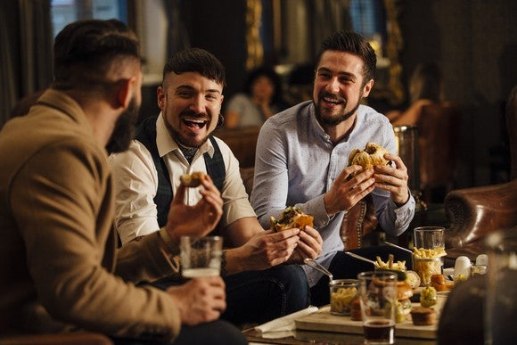 Three men eating at a bar.