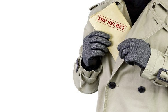 Man putting document marked Top Secret in his jacket