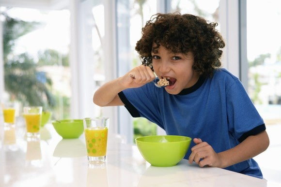A boy in a blue shirt leans over a green bowl on a counter as he lifts a spoonful of cereal to his mouth.