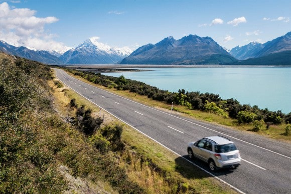 Car driving along a glacial lake in New Zealand, with relatively clear skies against a mountain backdrop.