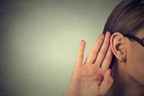 Woman listening with hand to ear
