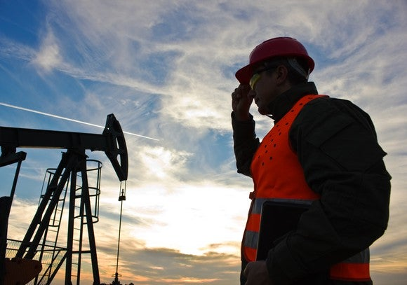 An oil worker holding a laptop while looking at an oil pump jack.