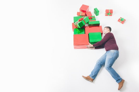 A man carries a huge load of wrapped presents in his arms, with several packages flying off the pile.