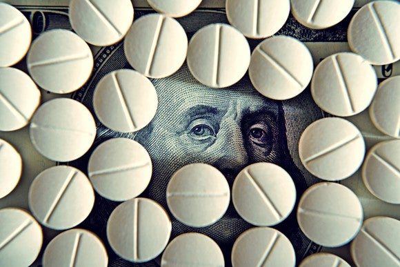 Prescription pills laid on top of a hundred dollar bill, with only Ben Franklin's eyes left visible.