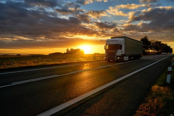Tractor trailer truck driving down road at sunset