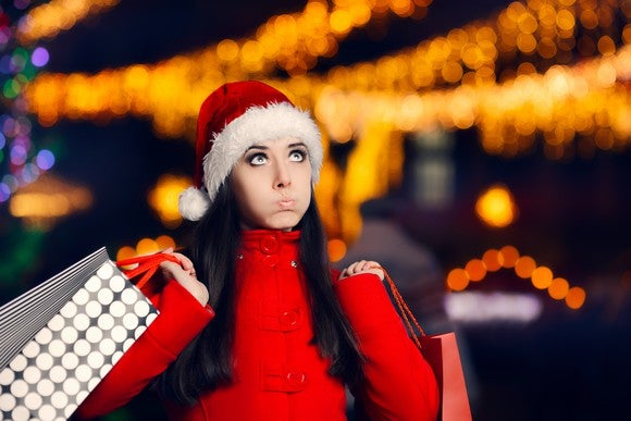 A woman puffs out her cheeks and looks upward while wearing a Santa hat and holding shopping bags.
