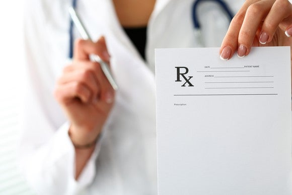Image of a female doctor holding a prescription pad.
