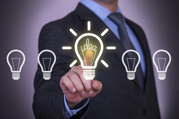 A man in a suit points at a lit up light bulb in a row of light bulbs.