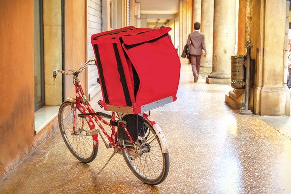 A delivery bike sits in the hallway of an office building.