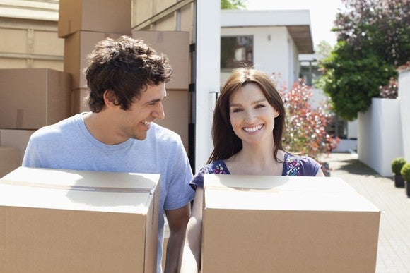 A young woman and man carrying boxes with a truck full of boxes and a house behind them.