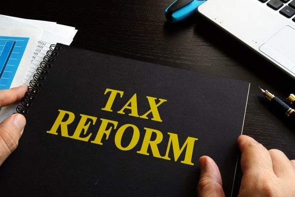 A person holding a binder with the title of tax reform.