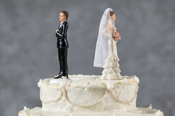 Wedding cake with bride and groom figurines facing away from each other.