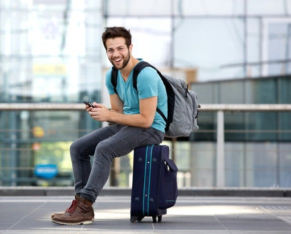 Man sitting on suitcase wearing backpack