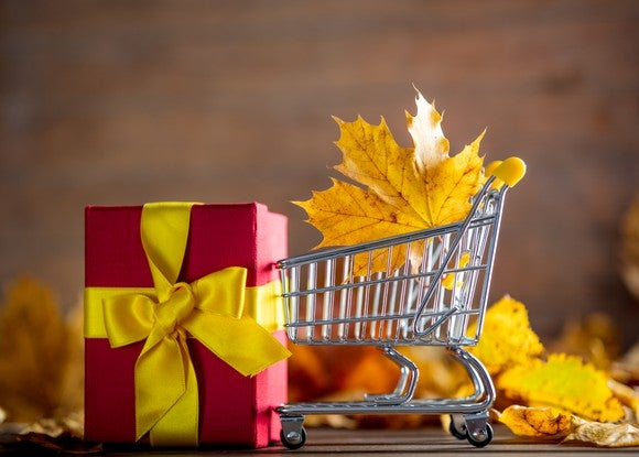 A maple leaf is in a tiny shopping cart near a small present.
