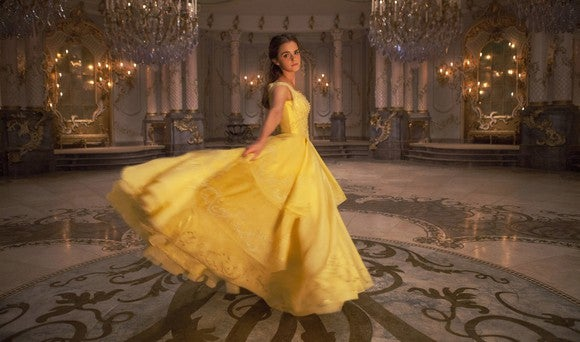 "Emma Watson as Belle in a yellow gown in a ballroom for ""Beauty and the Beast"" movie."