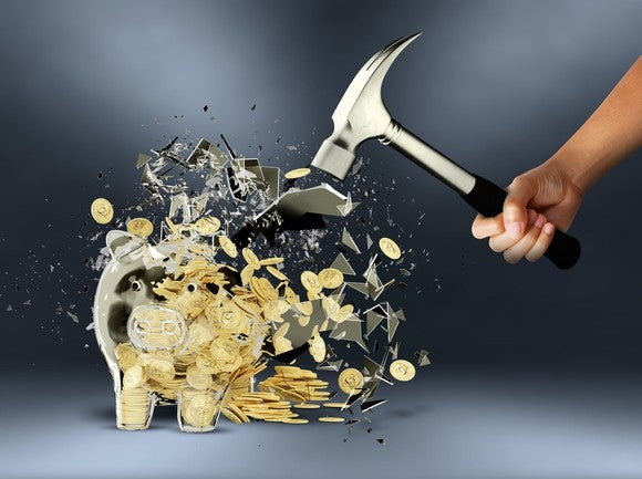hand with hammer smashes a golden piggy bank and coins spill out.