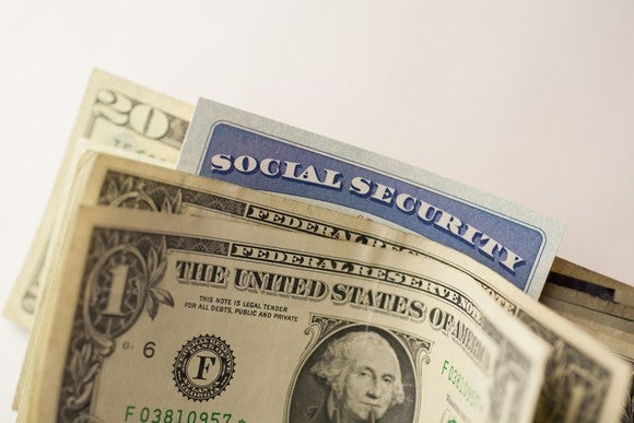A Social Security card poking out above a small stack of cash bills.