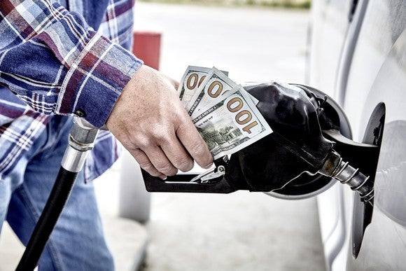 Man's hand holding three hundred US dollars and gas nozzle while pumping gas into parked vehicle.