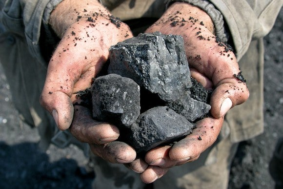 A person holds chunks of coal in his hands.