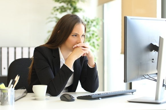Woman in suit jacket looking at computer screen