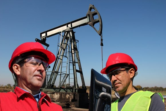 Oilfield workers next to a pump jack working with a laptop.