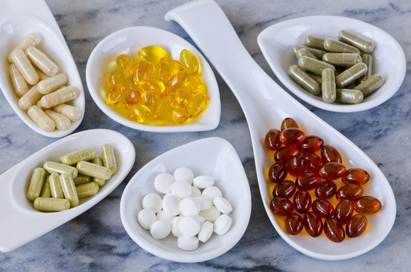 Nutrition supplements in bowls on a granite countertop.