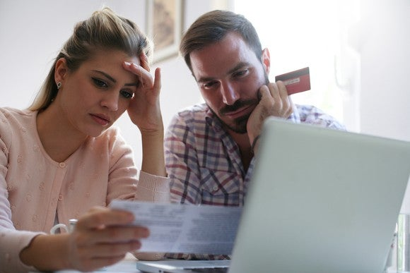 Woman looking concerned while holding a piece of paper and man looking concerned while holding a credit card