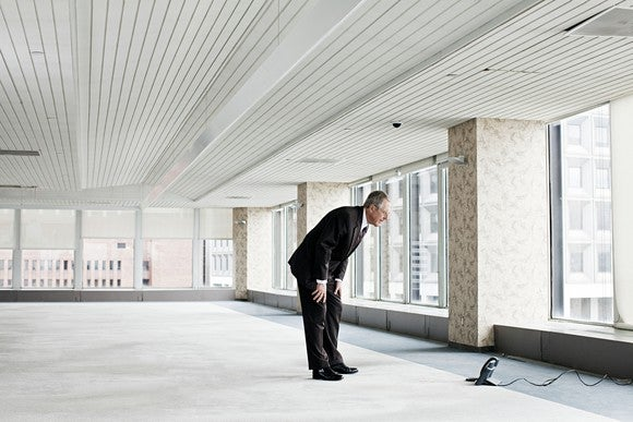 Older businessman staring at a phone in an empty office building