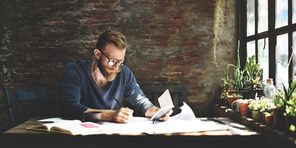 Man writing on a stack of papers and books in a home office.