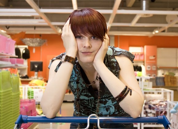 Woman resting on shopping cart in frustration