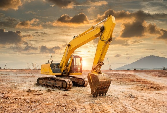A hydraulic excavator-loader machine at an earth-moving site.