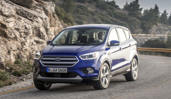 A blue 2017 Ford Kuga, a compact SUV, on a mountain road.