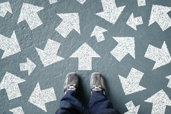 The point of view of someone looking down at their feet, and white arrows pointing in various directions are painted on the ground.