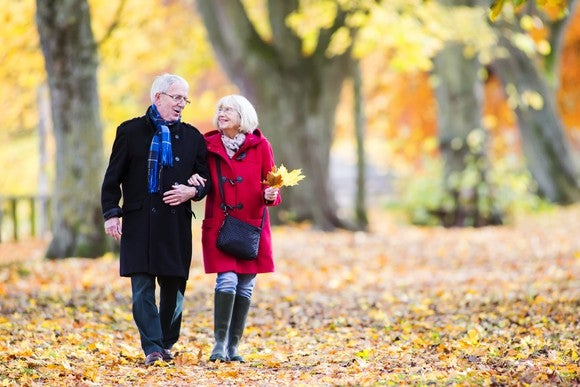 Senior couple walking in the woods with leaves on the ground in the fall