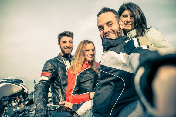 Smiling men and women by their motorcycles