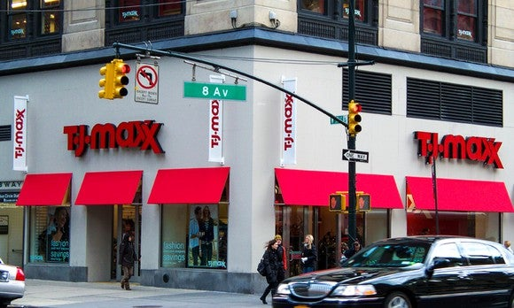 The outside of a TJ Maxx at an intersection in an urban setting. People and cars are passing by in the foreground.