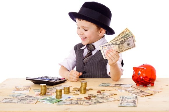 A kid in a tie and hat holds a wad of cash and looks at money on the table.