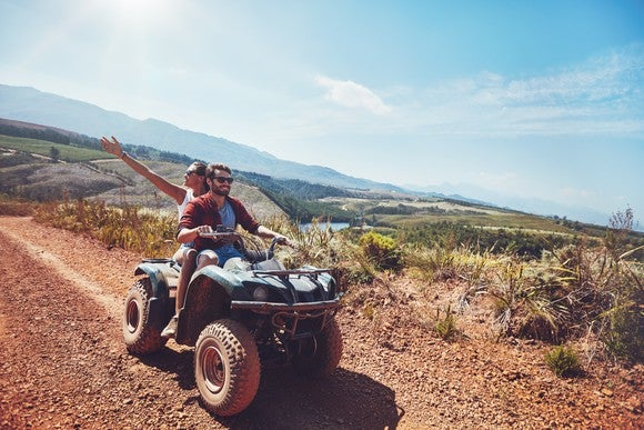 Off-road vehicle on a mountain road, with a man driving and a woman riding on back.