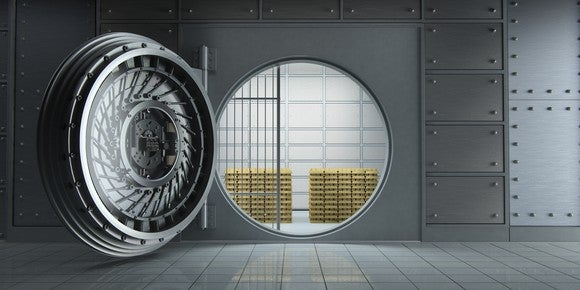 A bank vault with its door open and stacks of gold bars visible within
