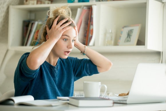 Woman at a laptop holding her head and looking shocked