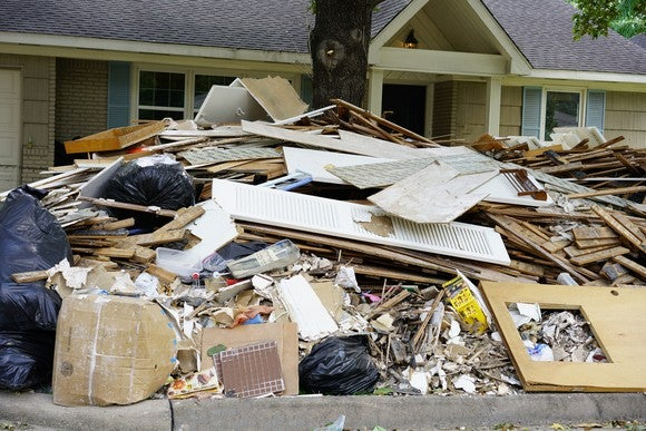 Piles of trash in front of a hurricane-damaged home