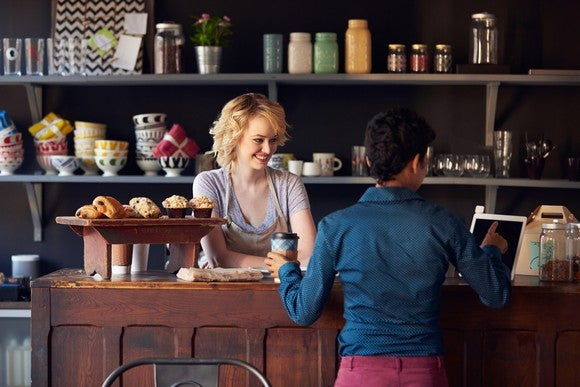 A woman in a bakery smiles from behind the counter as a customer completes her purchase on a point-of-sale terminal.