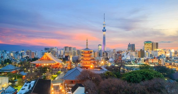 Colorful trees, a pagoda roofs, and the Tokyo skyline in the background