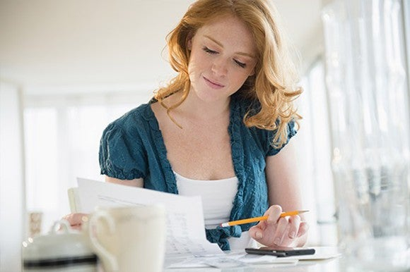 Woman with pencil staring at paper in brightly-lit kitchen.