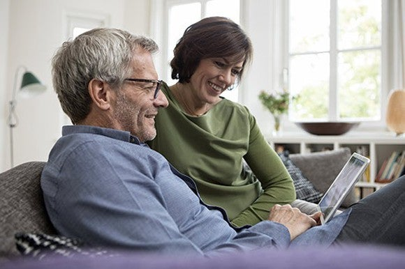 Couple sitting on couch staring at tablet, grinning. Window behind them in picture.