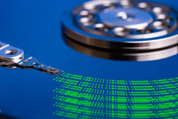 Close-up shot of a bare hard drive platter, where the read-and-write head is leaving green data traces on the black disk.