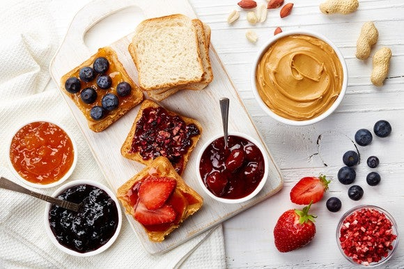 Peanut butter, jams, and jellies spread on a table